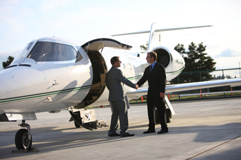 Private Jet from Switzerland, two men in suits shaking hands outside of the plane door.
